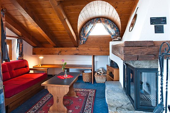 Suite Engiadina with balcony living room with fireplace – Hotel Chesa Grischa in Sils-Baselgia